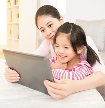 beautiful young mother and her cute daughter in shirts laughing and looking in digital tablet in the living room at home. family activity concept.